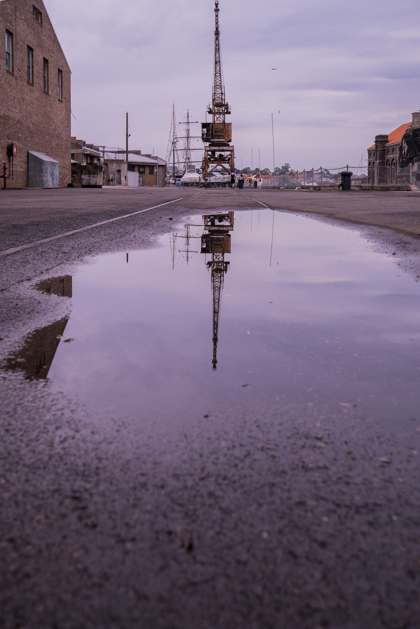 Reflection Of Crane In Puddle On Road