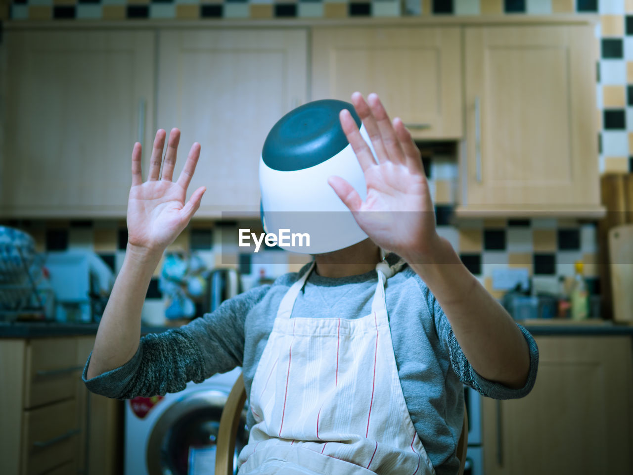 Man With Container On Head In Kitchen