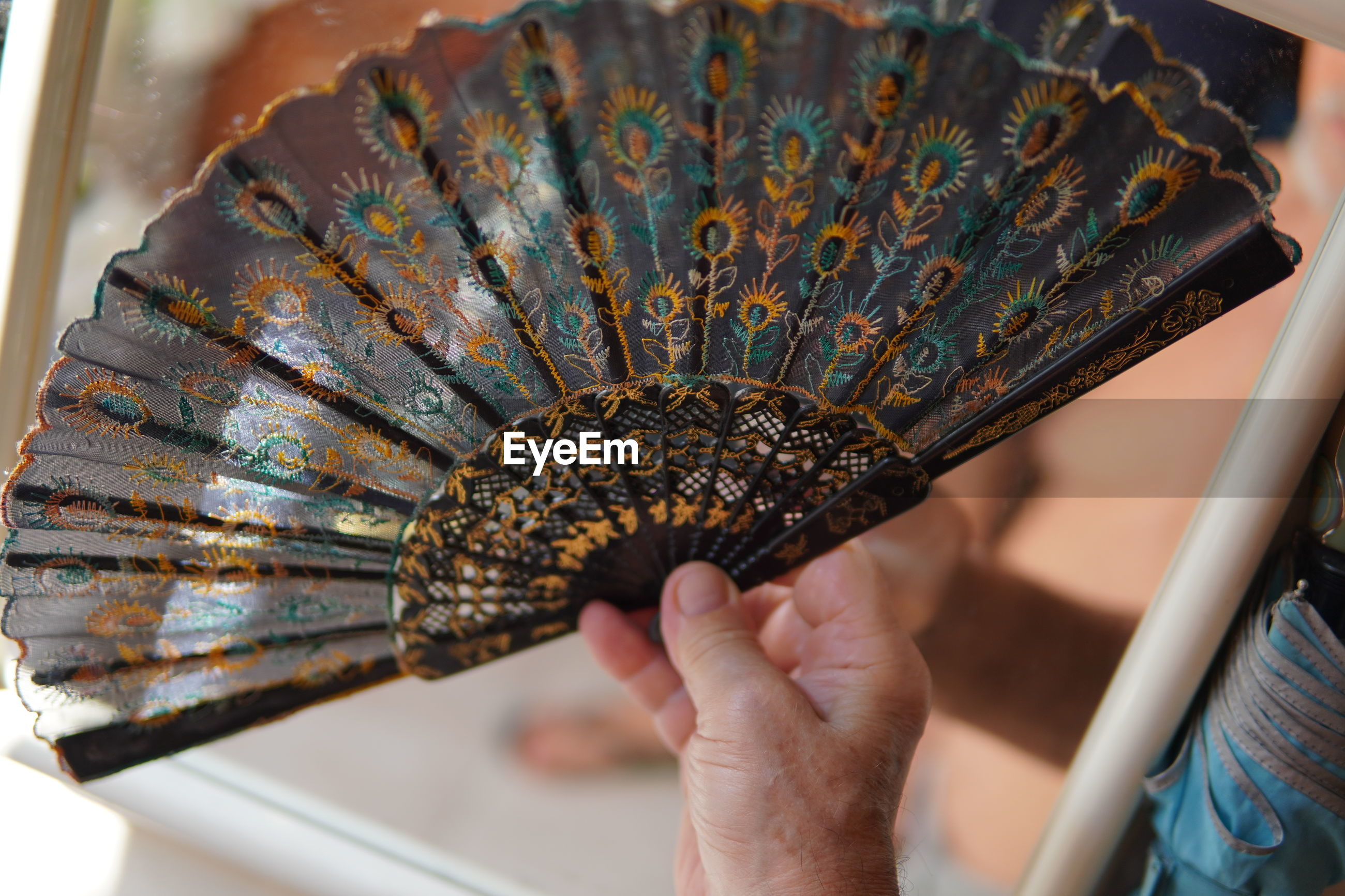 Close-up of hand holding hand fan