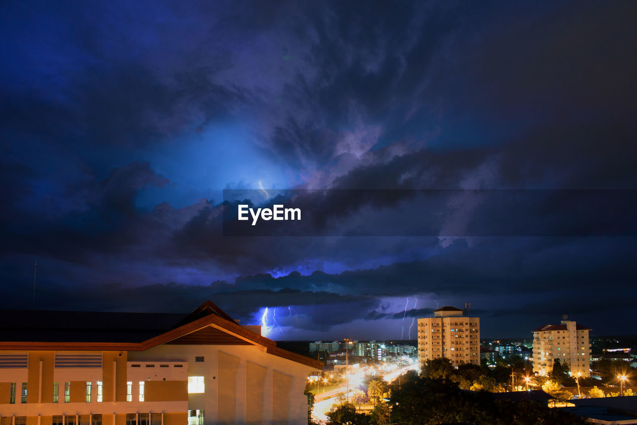 building exterior, architecture, built structure, cloud - sky, building, sky, illuminated, night, storm, city, residential district, nature, no people, house, storm cloud, thunderstorm, overcast, outdoors, dramatic sky, power in nature, ominous