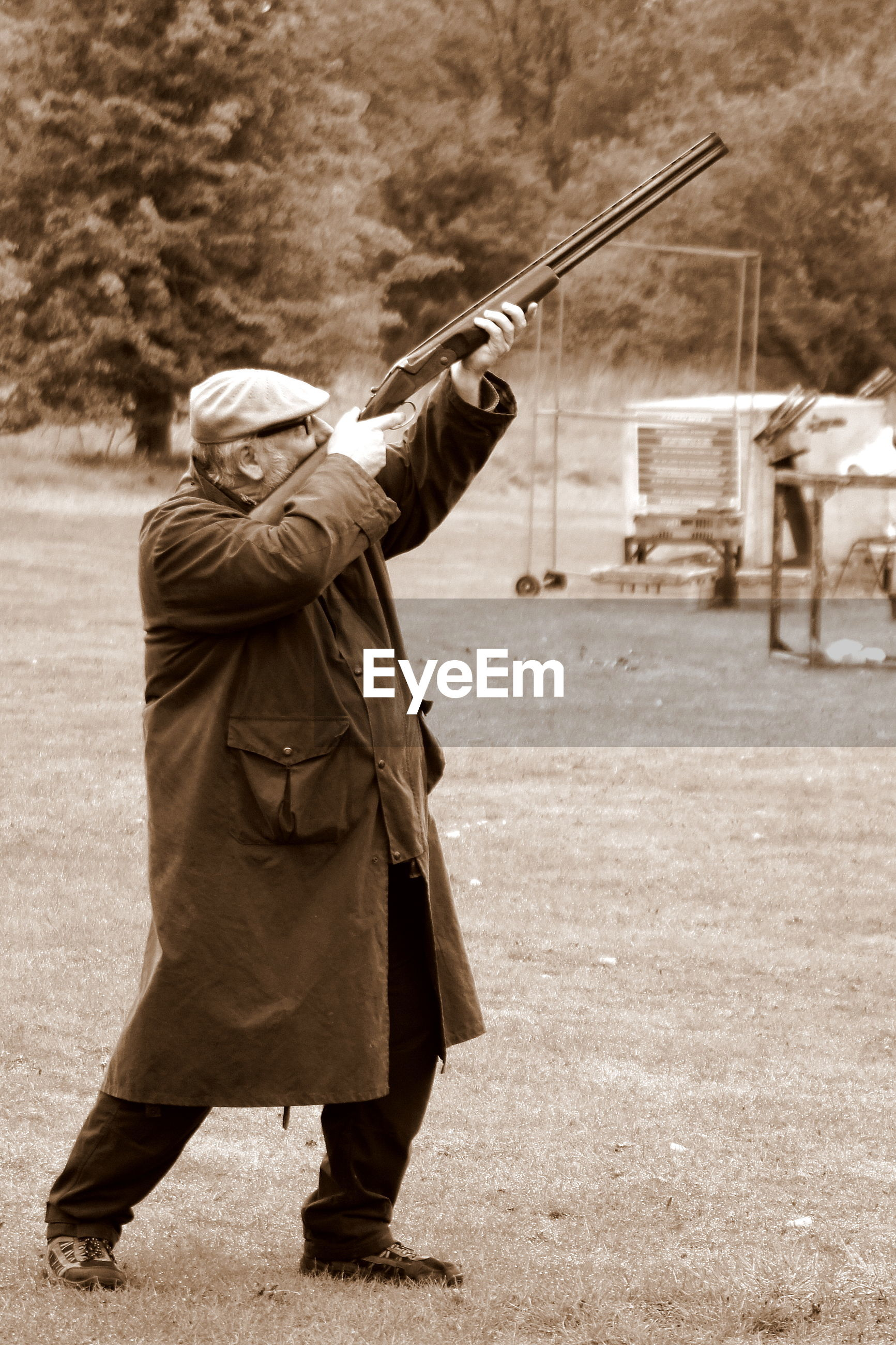 Side view of senior man aiming gun while standing on grassy field