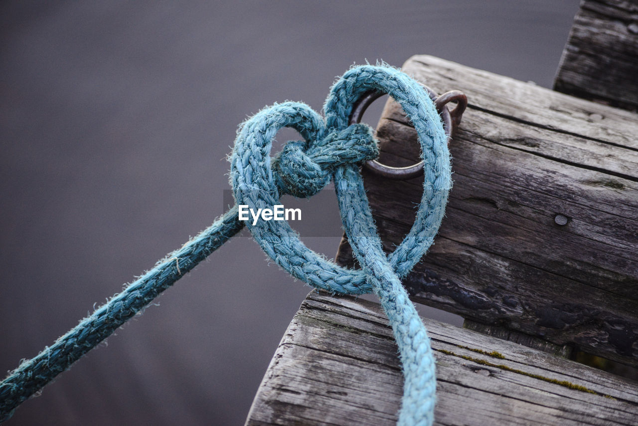 Close-Up Of Rope Tied To Ring Bollard On Wood
