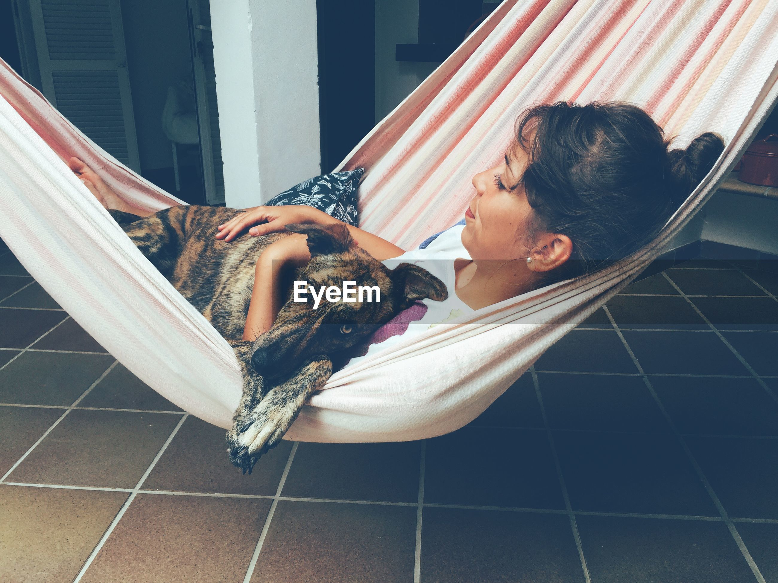 Woman relaxing in hammock with her dog