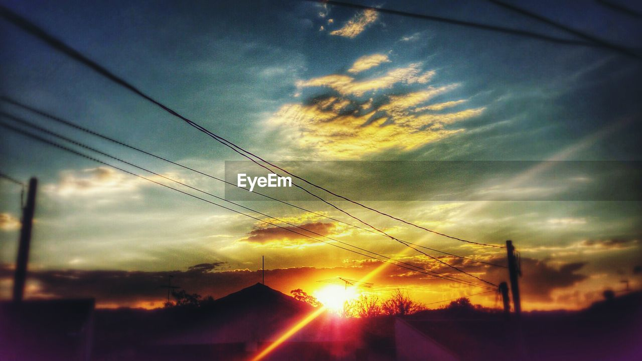 cloud - sky, sky, sunset, sunbeam, sun, silhouette, nature, cable, outdoors, scenics, sunlight, beauty in nature, tranquility, no people, tree, electricity pylon, day