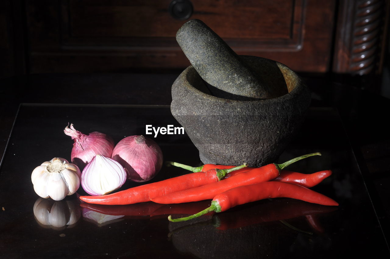 vegetable, freshness, spice, flower, indoors, chili pepper, plant, red, flowering plant, no people, ingredient, pepper, red chili pepper, still life, close-up, food, beauty in nature, garlic, mortar and pestle, petal