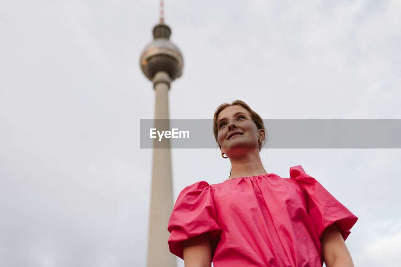 Low angle view of woman looking away against tower and sky