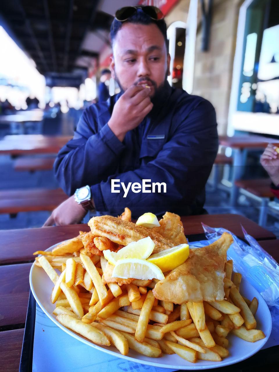 Man Eating Fast Food At Restaurant