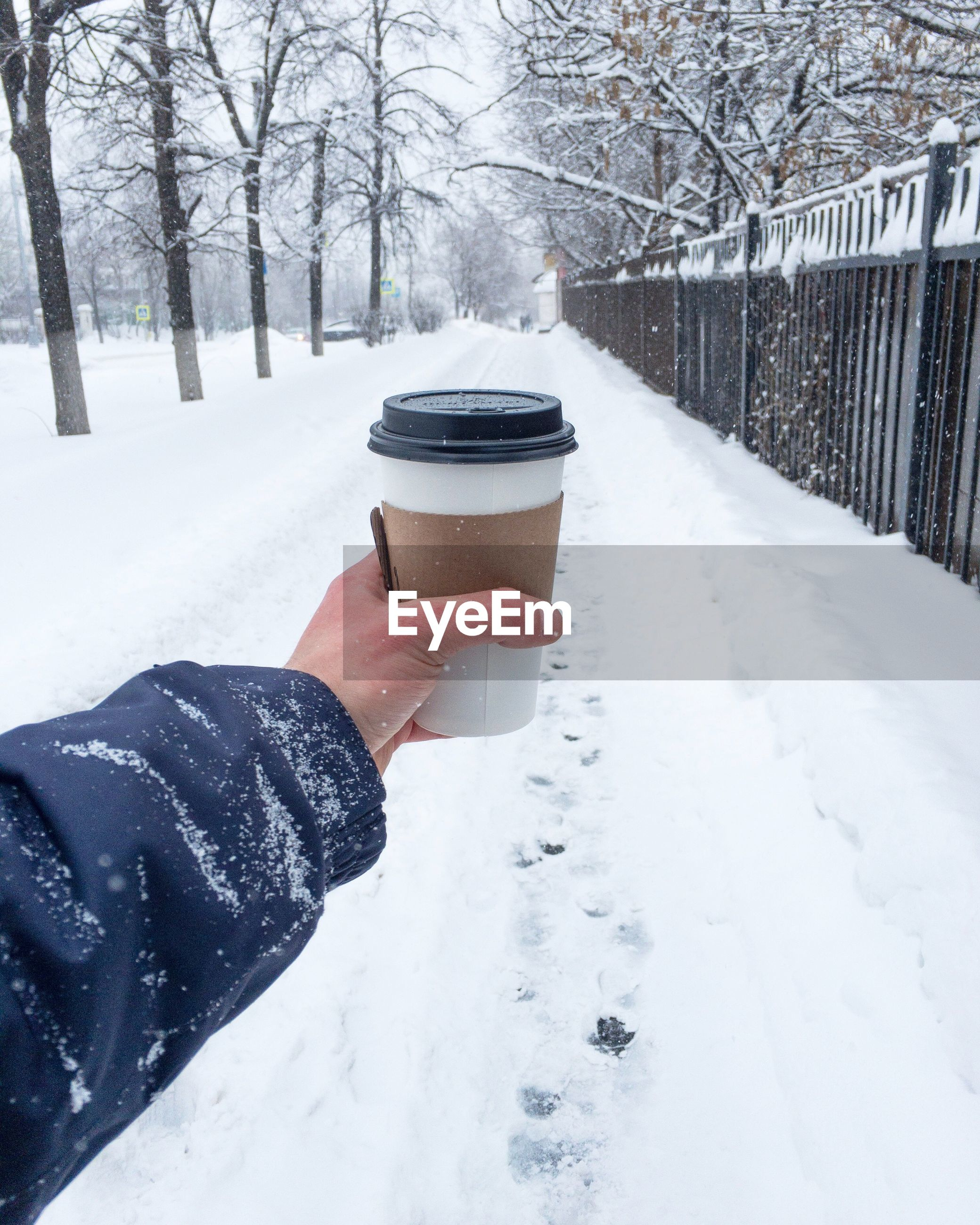 Cropped hand having coffee on snow covered road