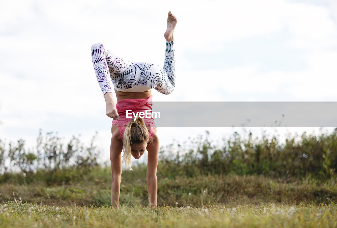 one person, full length, real people, leisure activity, grass, lifestyles, field, land, casual clothing, day, plant, nature, sky, women, balance, handstand, child, vitality, human arm, outdoors, arms raised