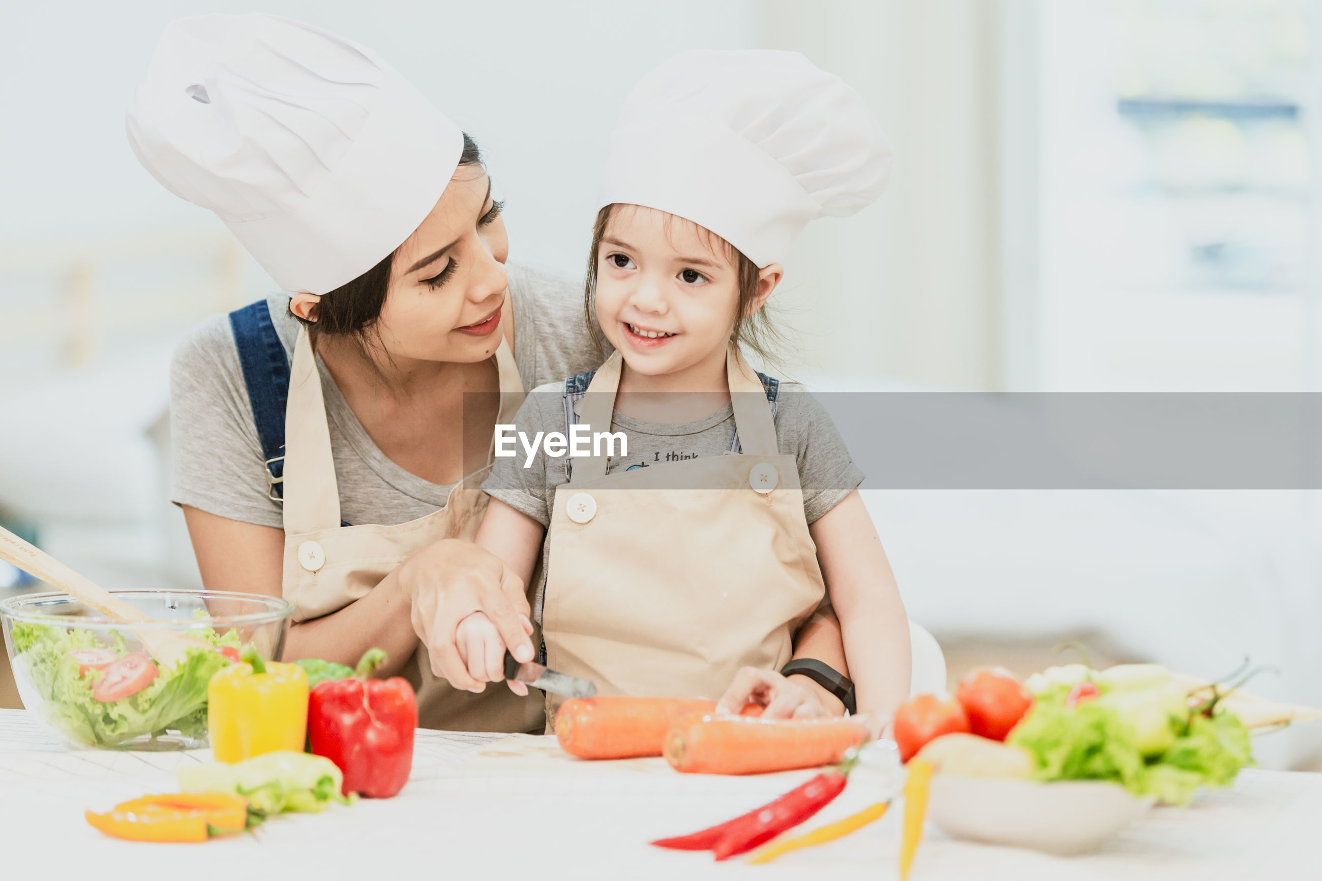 Mother and daughter preparing food on table