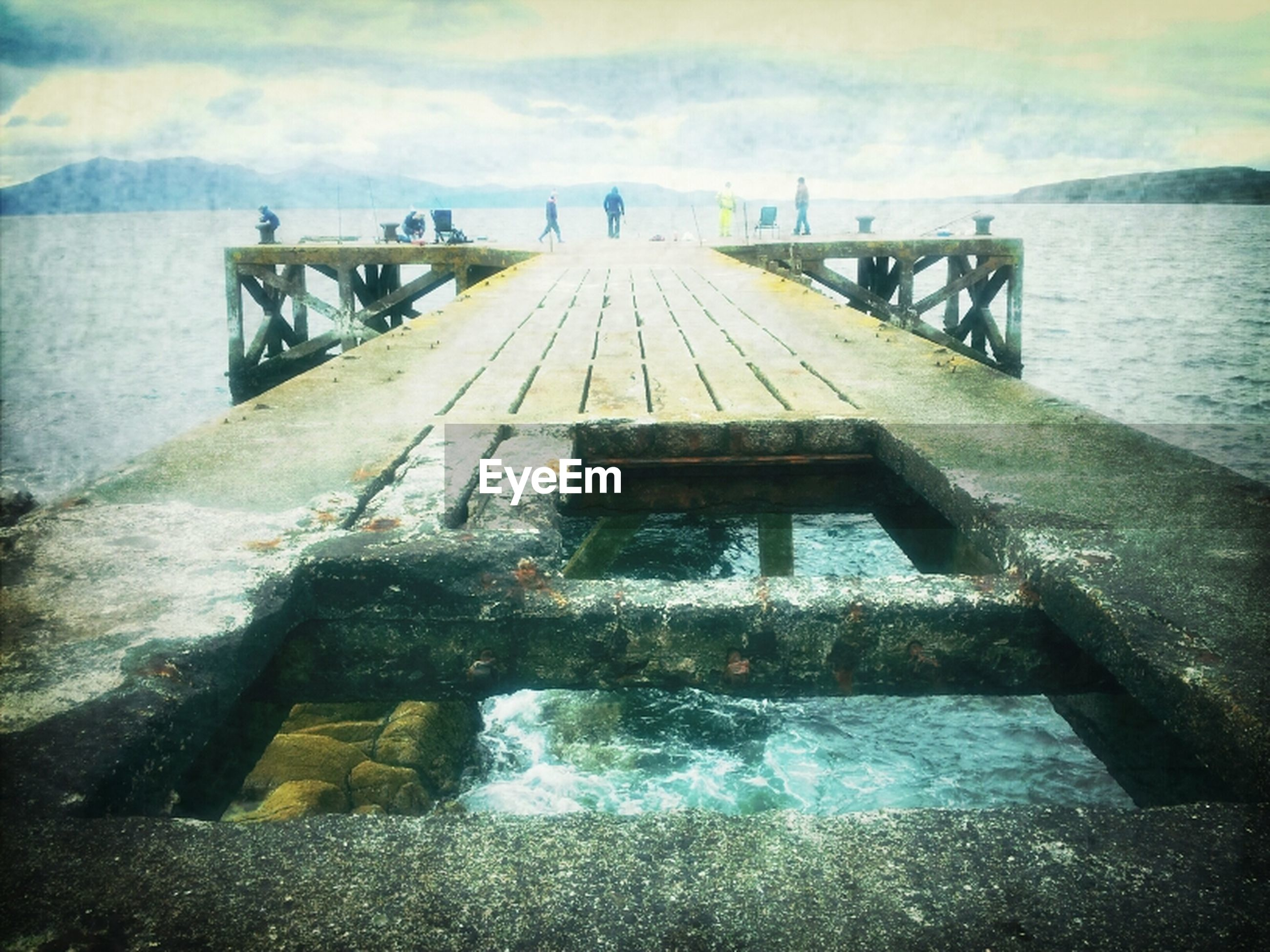water, sky, sea, built structure, cloud - sky, architecture, pier, tranquility, nature, railing, tranquil scene, bridge - man made structure, scenics, connection, river, rock - object, cloudy, beauty in nature, wood - material, outdoors