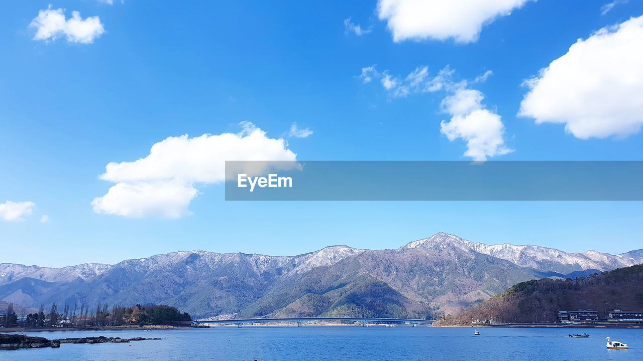 mountain, sky, water, scenics - nature, cloud - sky, beauty in nature, mountain range, waterfront, tranquil scene, nature, tranquility, day, blue, no people, non-urban scene, idyllic, cold temperature, lake, travel destinations, outdoors, snowcapped mountain, mountain peak