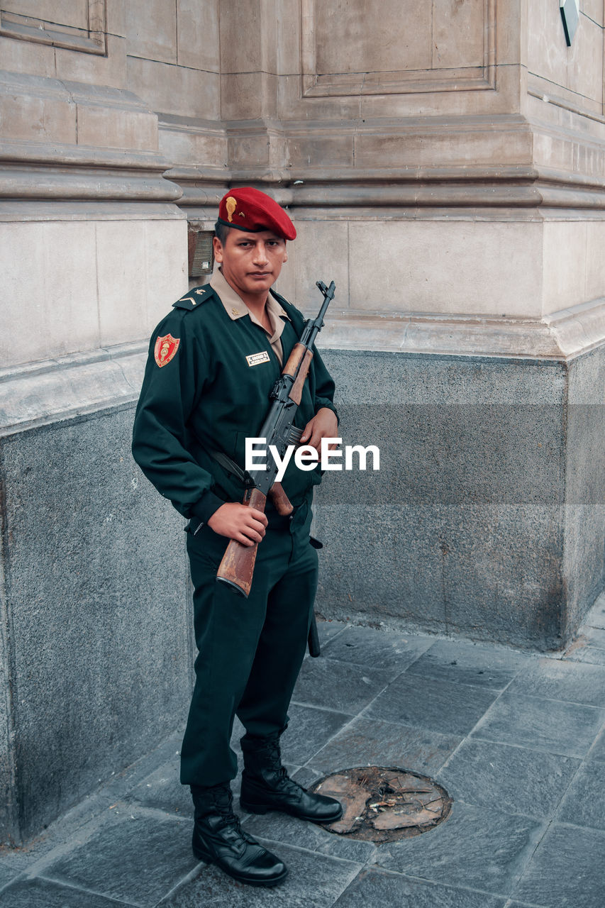 full length, holding, one person, real people, standing, clothing, day, front view, weapon, architecture, portrait, looking at camera, cap, leisure activity, uniform, men, one animal, boys, government
