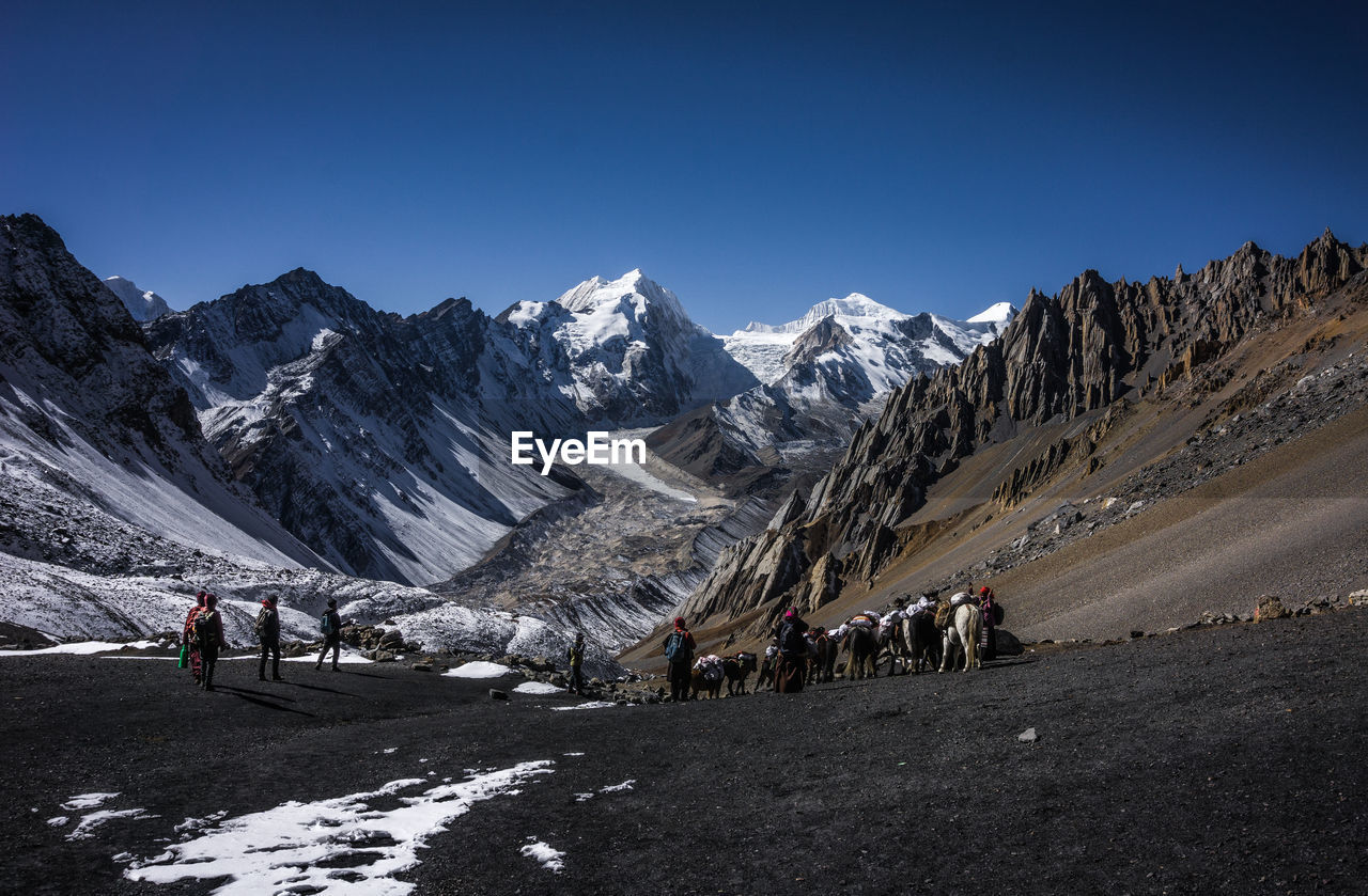 mountain, group of people, snow, winter, sky, cold temperature, scenics - nature, real people, leisure activity, mountain range, beauty in nature, nature, clear sky, landscape, snowcapped mountain, lifestyles, environment, adventure, people, outdoors