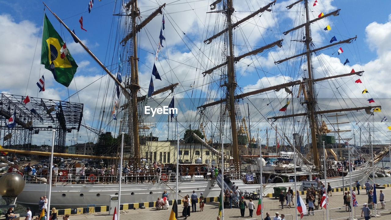 flag, group of people, mode of transportation, built structure, nautical vessel, transportation, sky, day, crowd, pole, real people, architecture, sailboat, nature, large group of people, mast, patriotism, building exterior, water, outdoors
