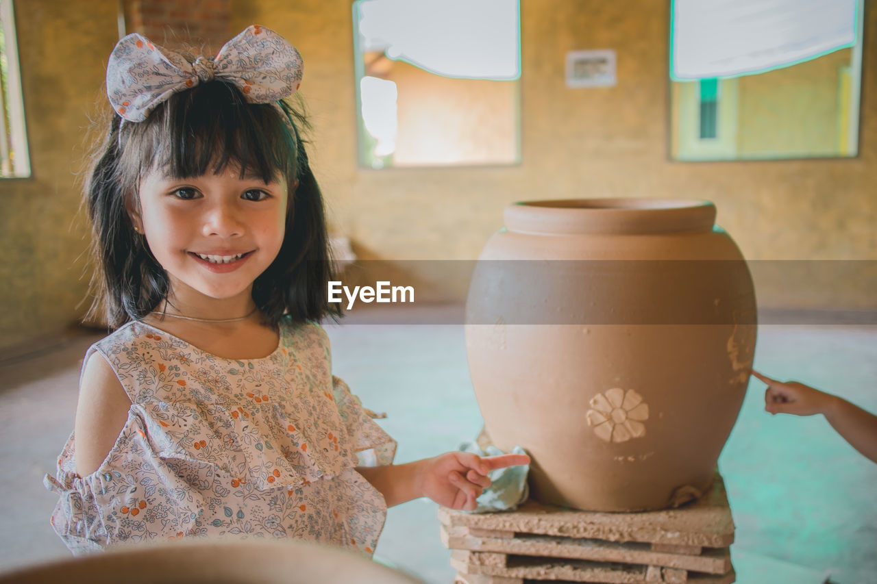 Portrait of smiling girl showing pottery in workshop