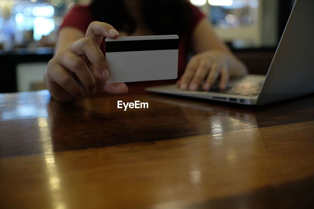 Midsection of woman holding credit card while online shopping at wooden table