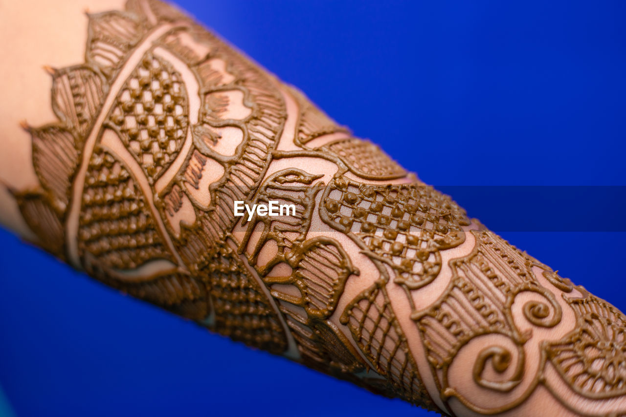 Close-up of woman hand with henna tattoo against blue background