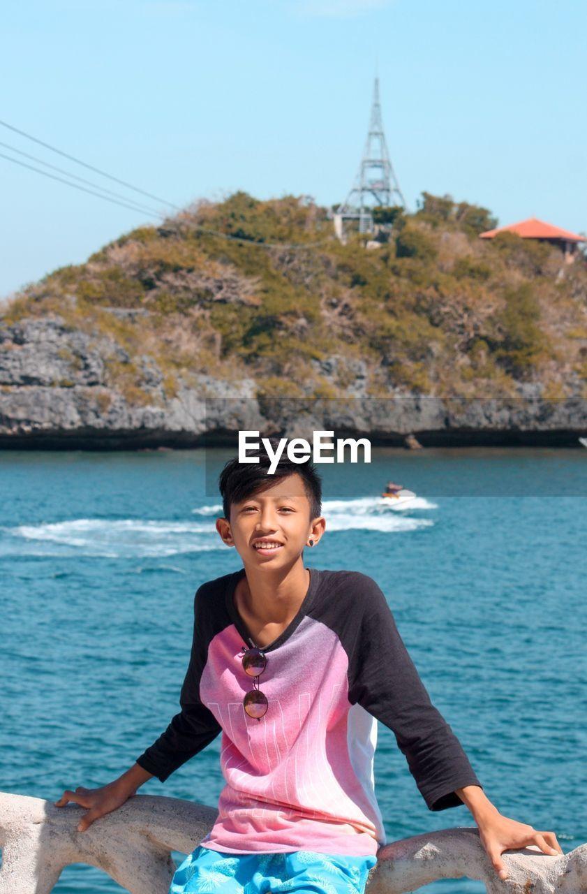 Portrait of smiling teenage boy standing against sea