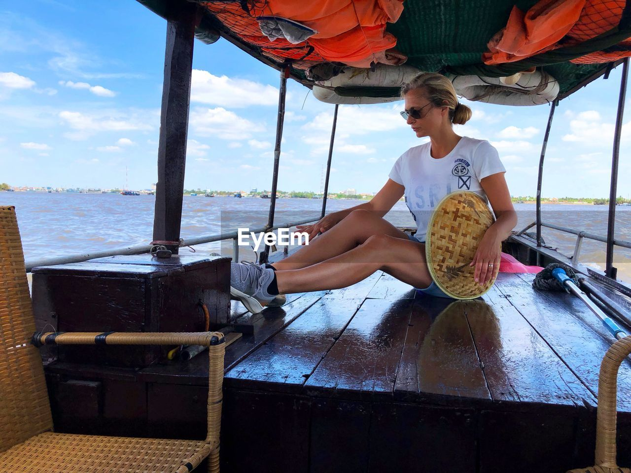 real people, leisure activity, sitting, lifestyles, water, one person, day, women, child, young women, nature, casual clothing, childhood, young adult, sky, food and drink, nautical vessel, outdoors