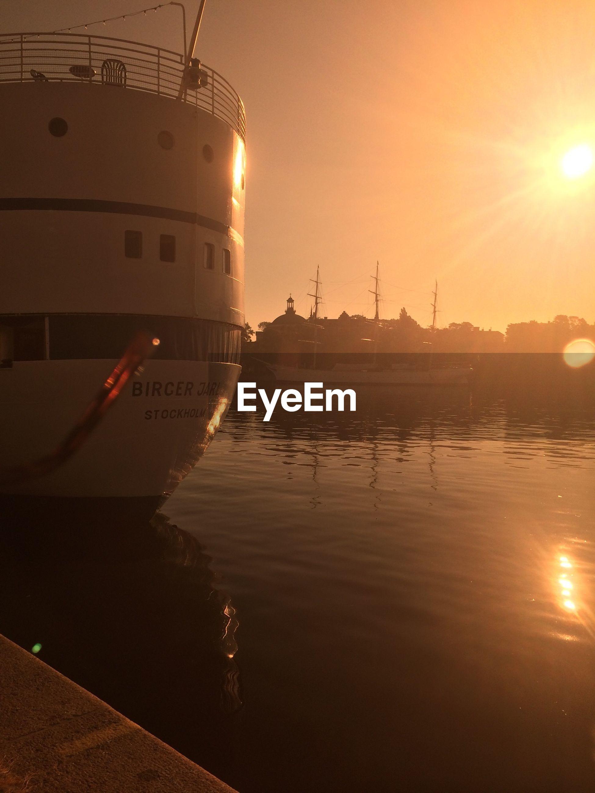 sunset, sun, water, nautical vessel, transportation, boat, mode of transport, reflection, moored, sea, orange color, sunlight, mast, sky, sunbeam, waterfront, lens flare, harbor, sailboat, nature