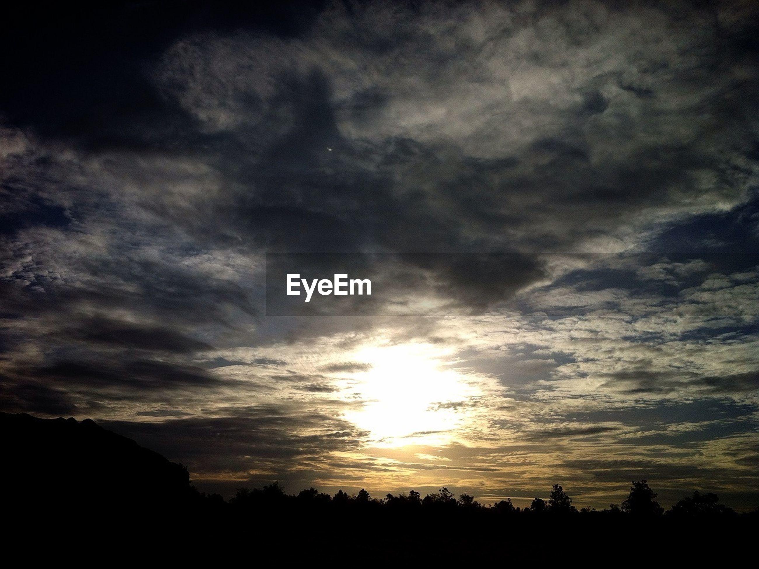silhouette, sky, sunset, beauty in nature, cloud - sky, tranquil scene, scenics, tranquility, nature, cloudy, sun, cloud, landscape, tree, idyllic, low angle view, sunlight, dramatic sky, dark, outdoors