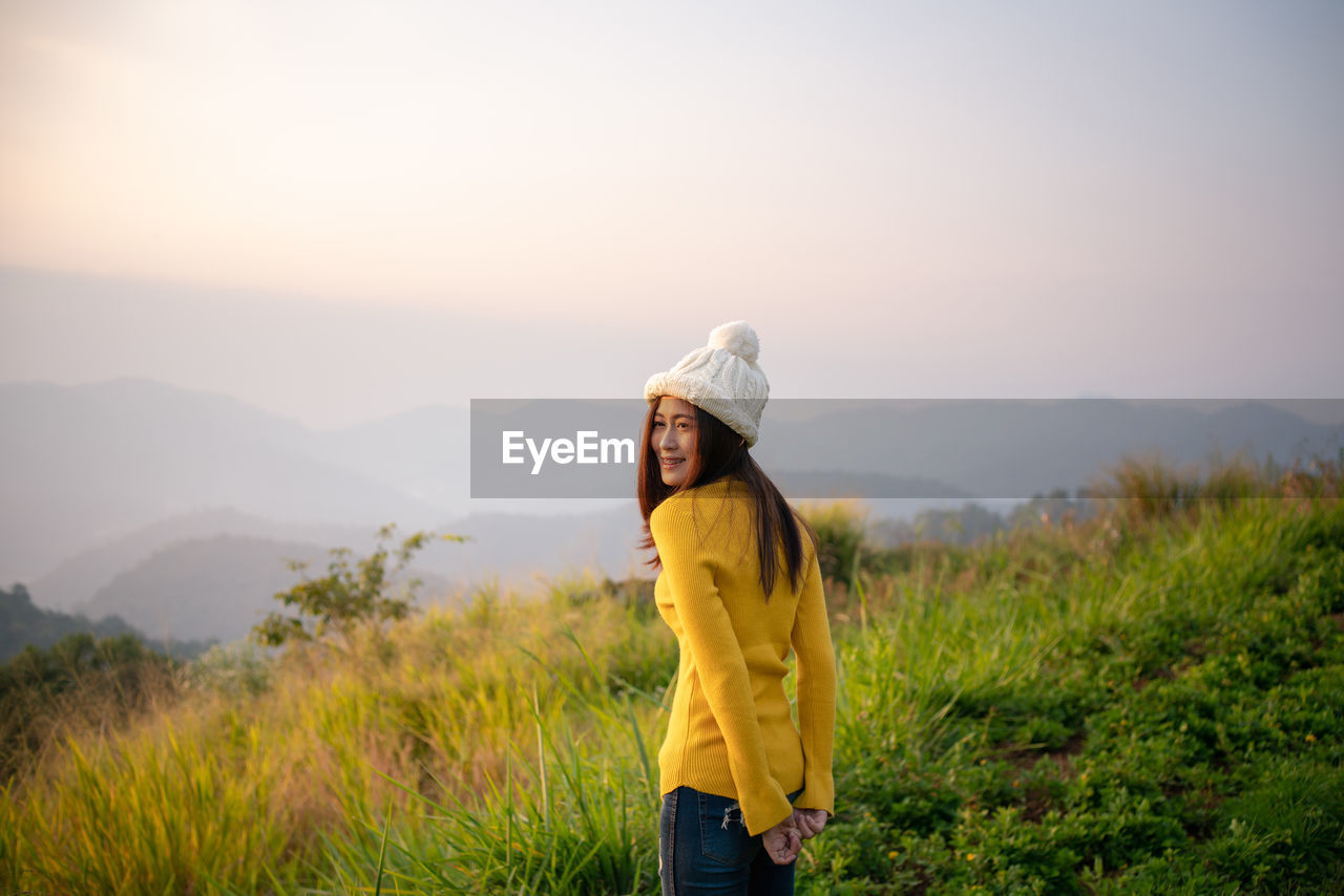 one person, real people, standing, lifestyles, leisure activity, beauty in nature, three quarter length, casual clothing, sky, plant, nature, clothing, young adult, smiling, field, scenics - nature, mountain, non-urban scene, yellow, outdoors