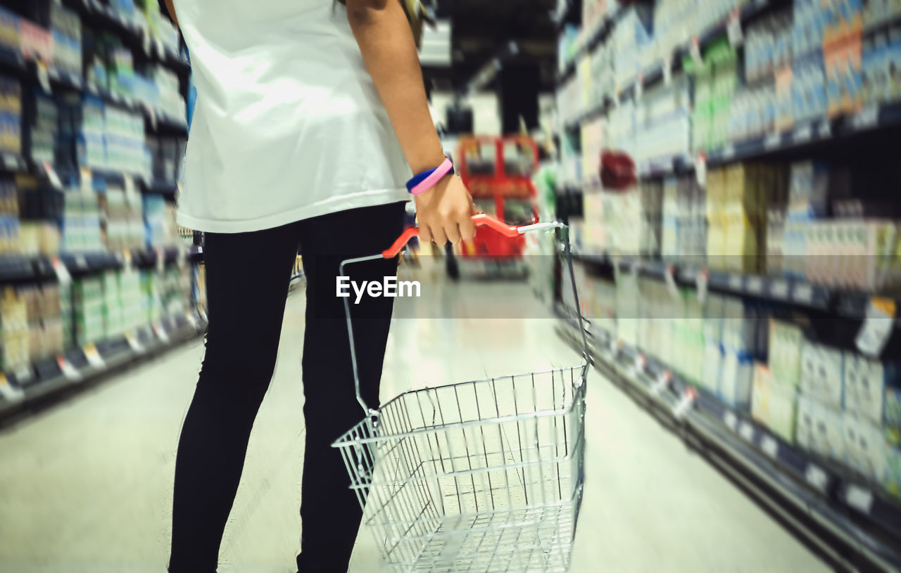 Midsection Of Woman With Basket In Supermarket