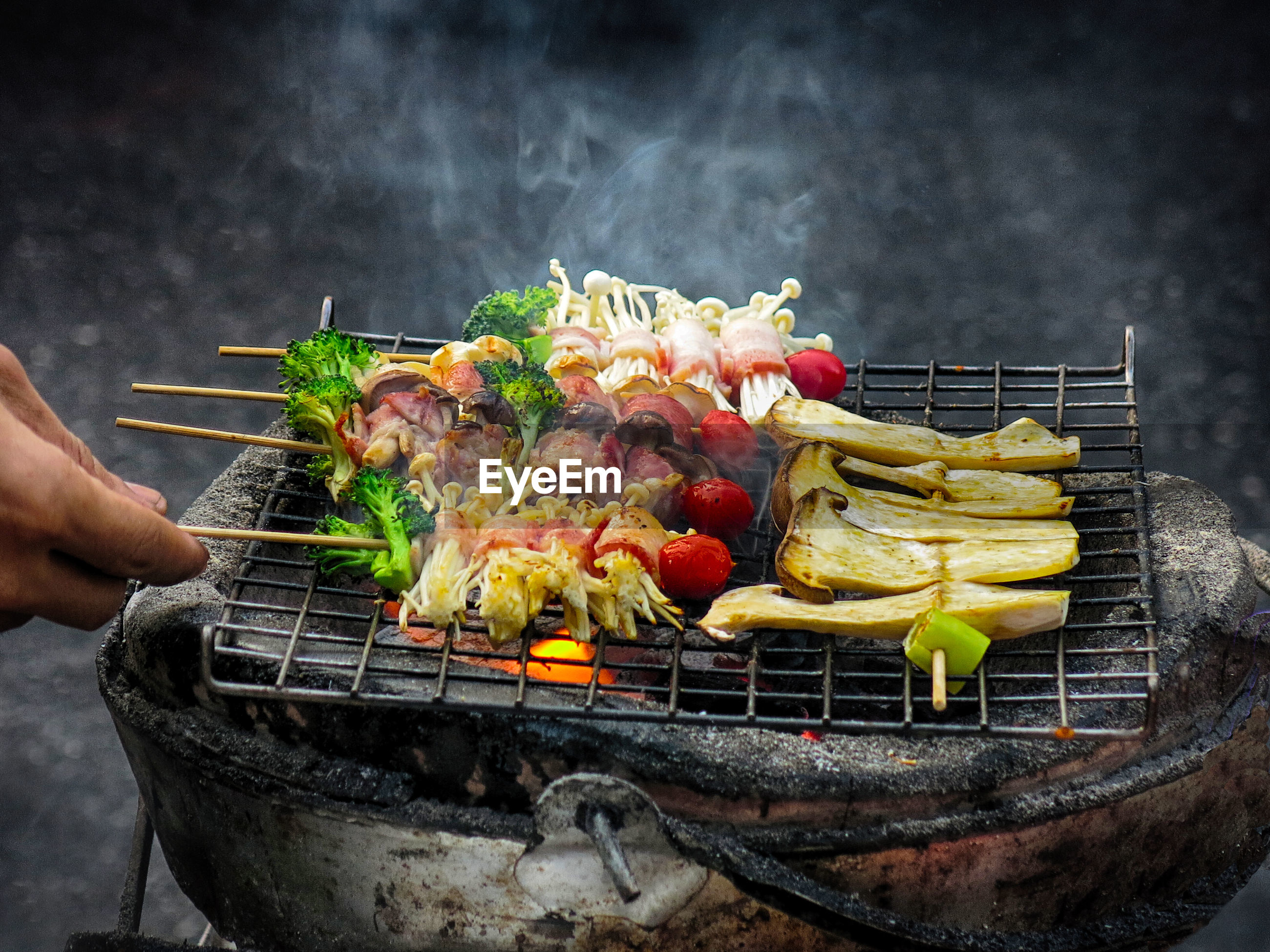 Cropped image of person cooking vegetables on barbecue grill
