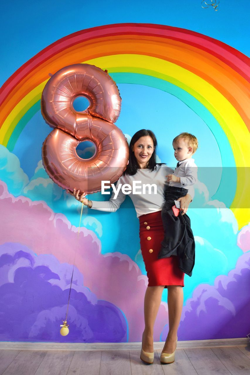Portrait of mother with son holding number 8 inflatable ring against mural
