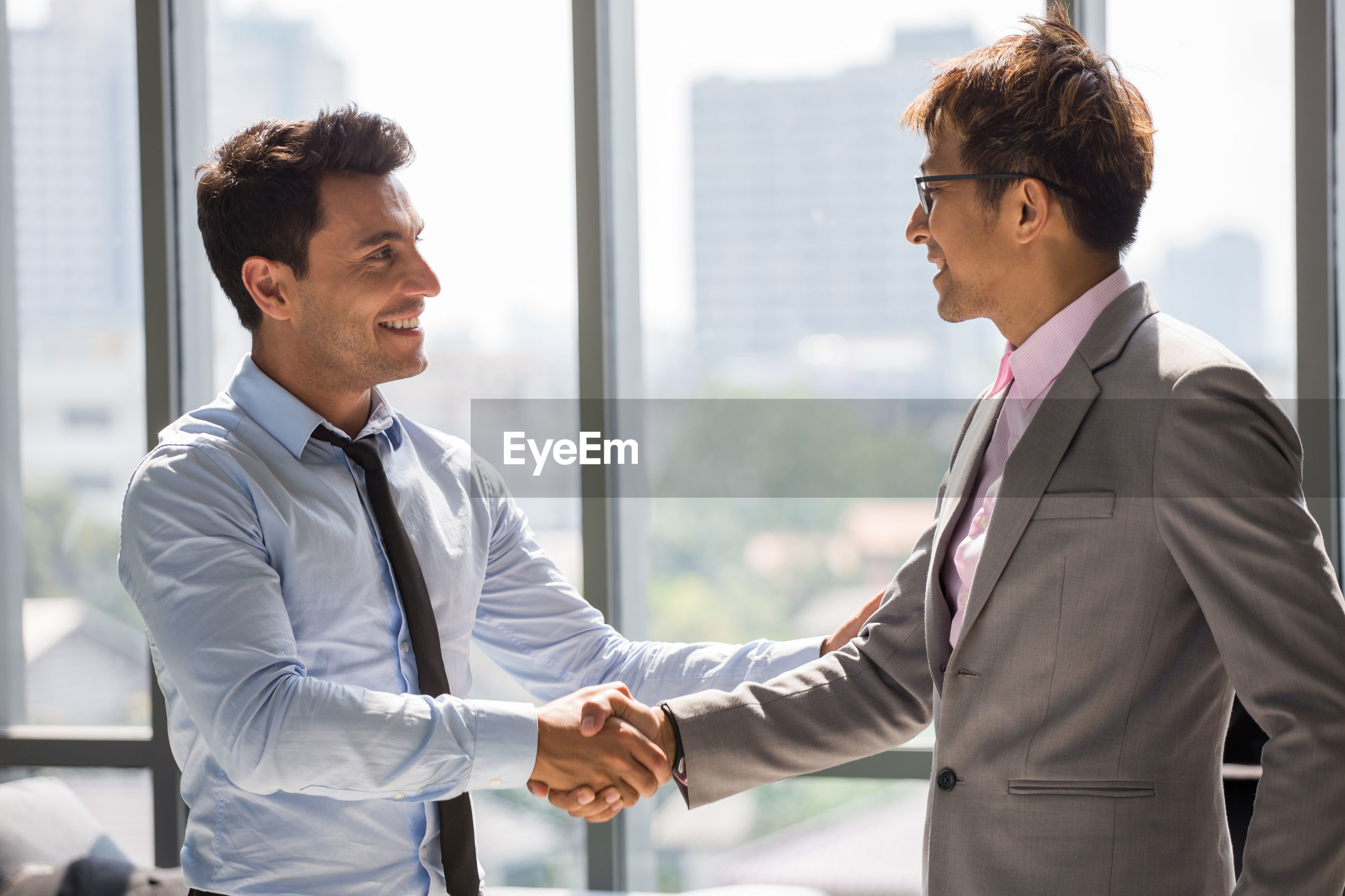 Side view of smiling business people shaking hands
