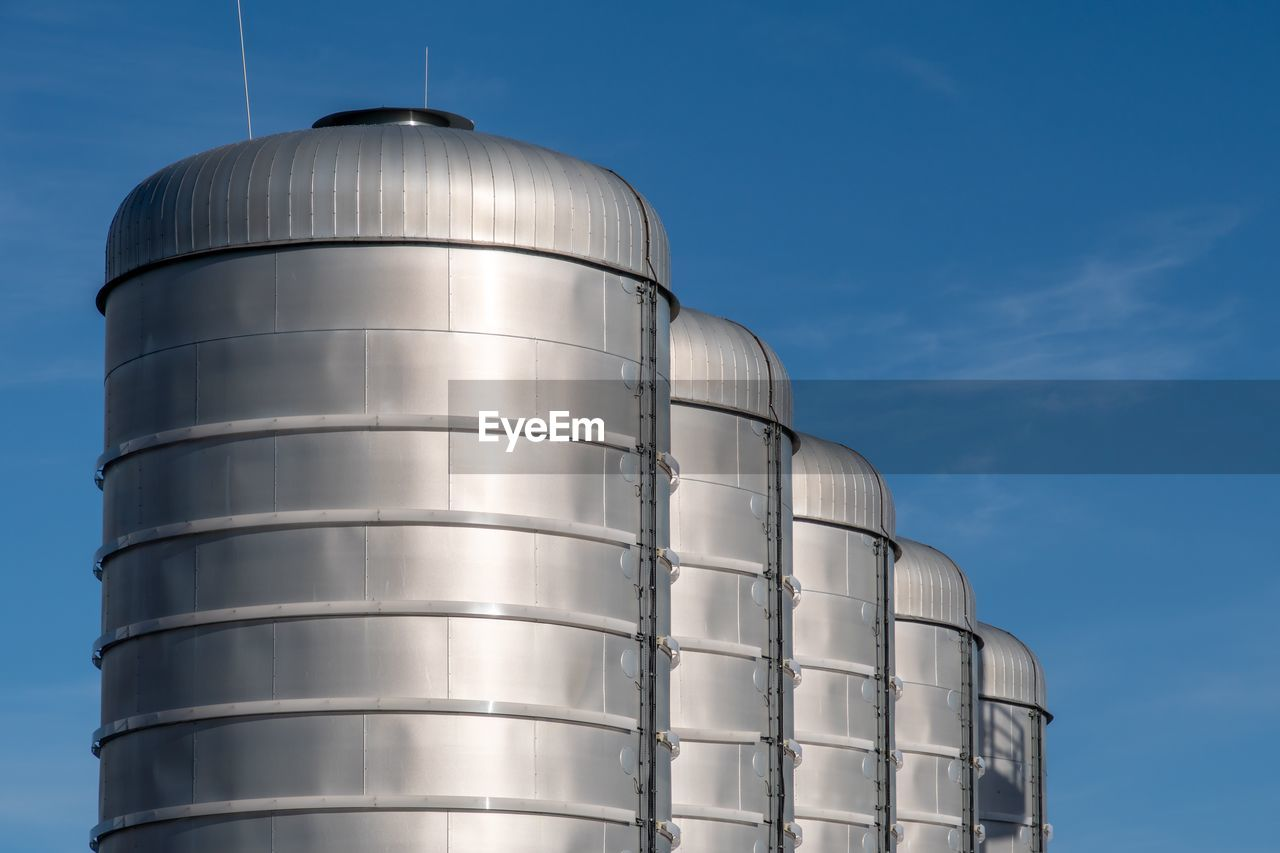 sky, low angle view, nature, factory, no people, storage tank, industry, metal, day, storage compartment, blue, food and drink, agriculture, silo, sunlight, silver colored, built structure, architecture, cylinder, fuel storage tank, steel
