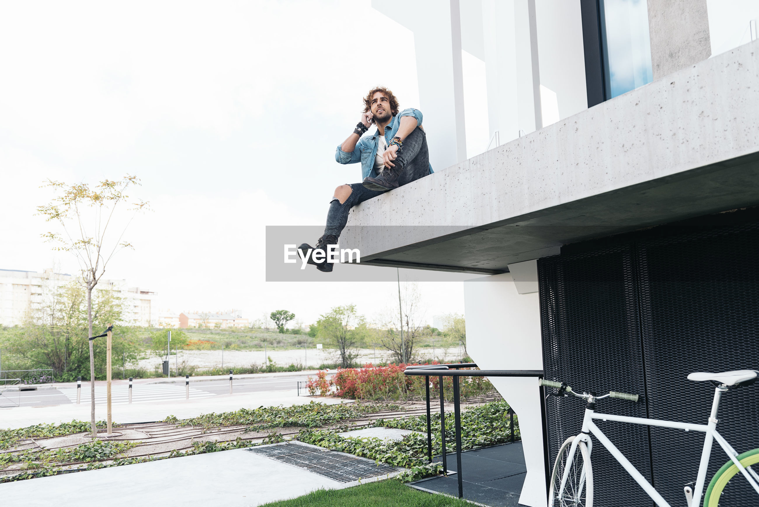 Low angle view of man using phone while sitting at building balcony