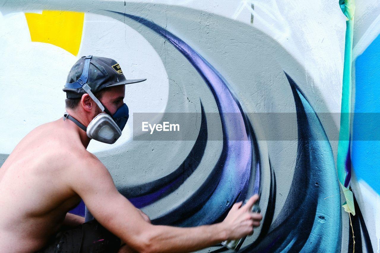 Side View Of Man Spraying Graffiti