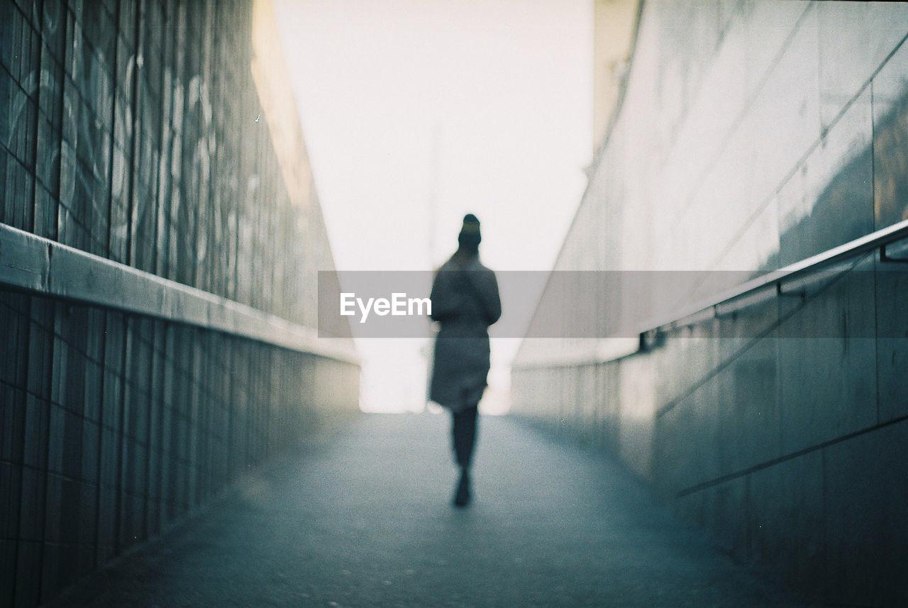Rear view of woman walking on underground walkway