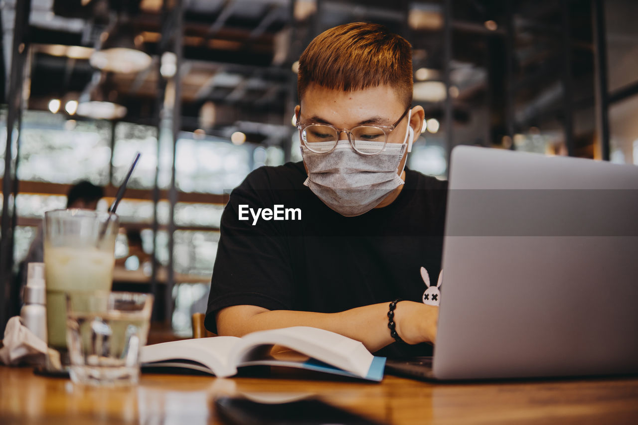 Young man wearing mask using laptop at cafe