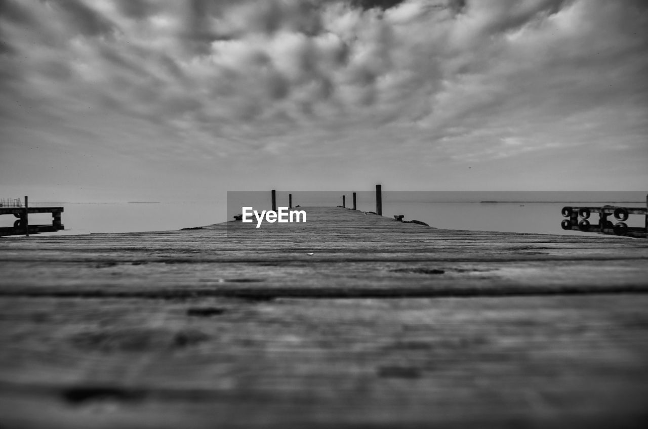 sky, cloud - sky, pier, wood - material, water, sea, selective focus, nature, direction, day, the way forward, outdoors, built structure, scenics - nature, tranquil scene, beauty in nature, no people, tranquility, beach, diminishing perspective, surface level, wood, long, wooden post