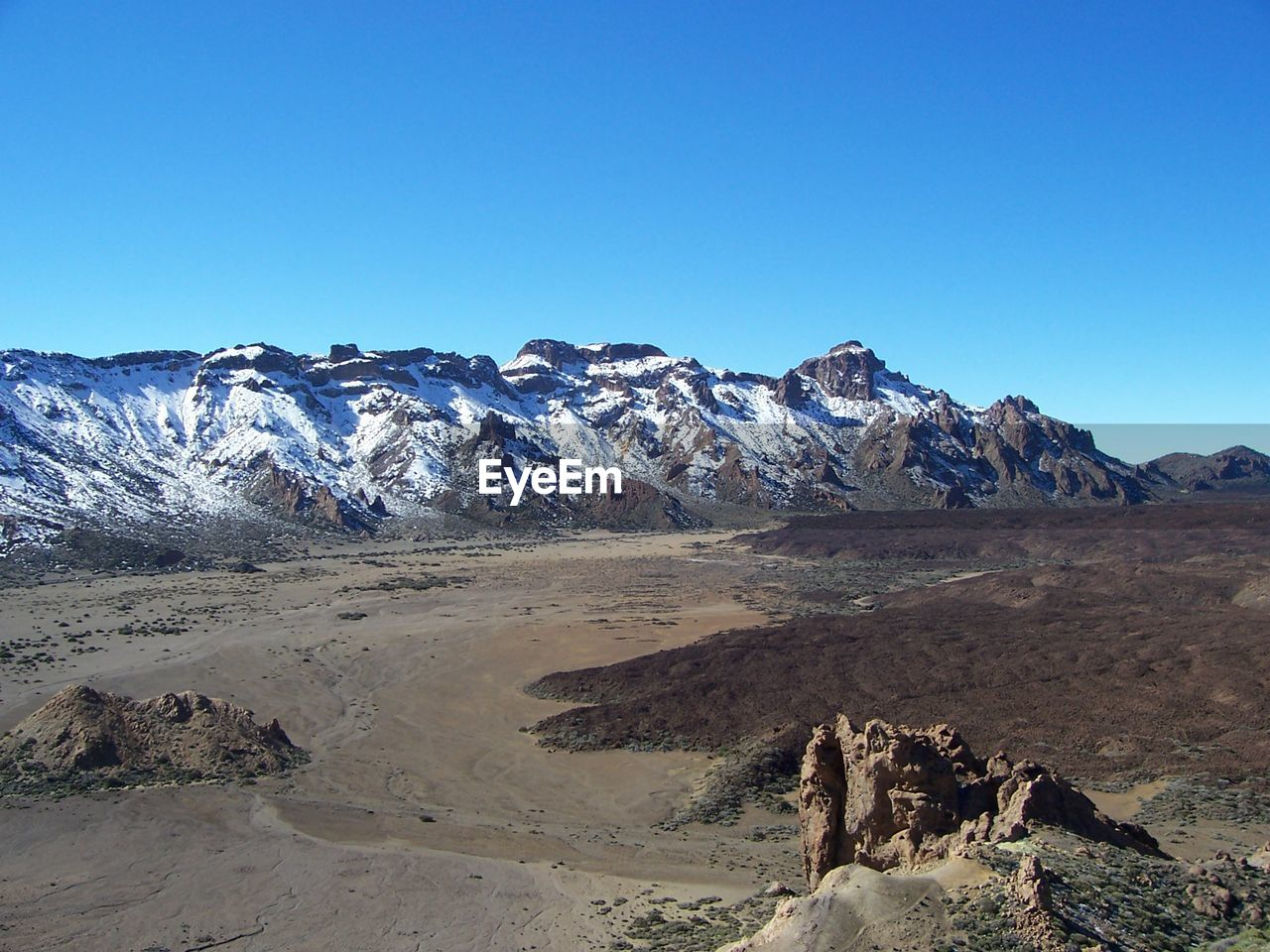 sky, clear sky, mountain, scenics - nature, blue, tranquil scene, beauty in nature, copy space, tranquility, nature, non-urban scene, landscape, day, environment, mountain range, remote, rock, idyllic, no people, geology, arid climate, outdoors, climate, formation, snowcapped mountain, mountain peak, eroded