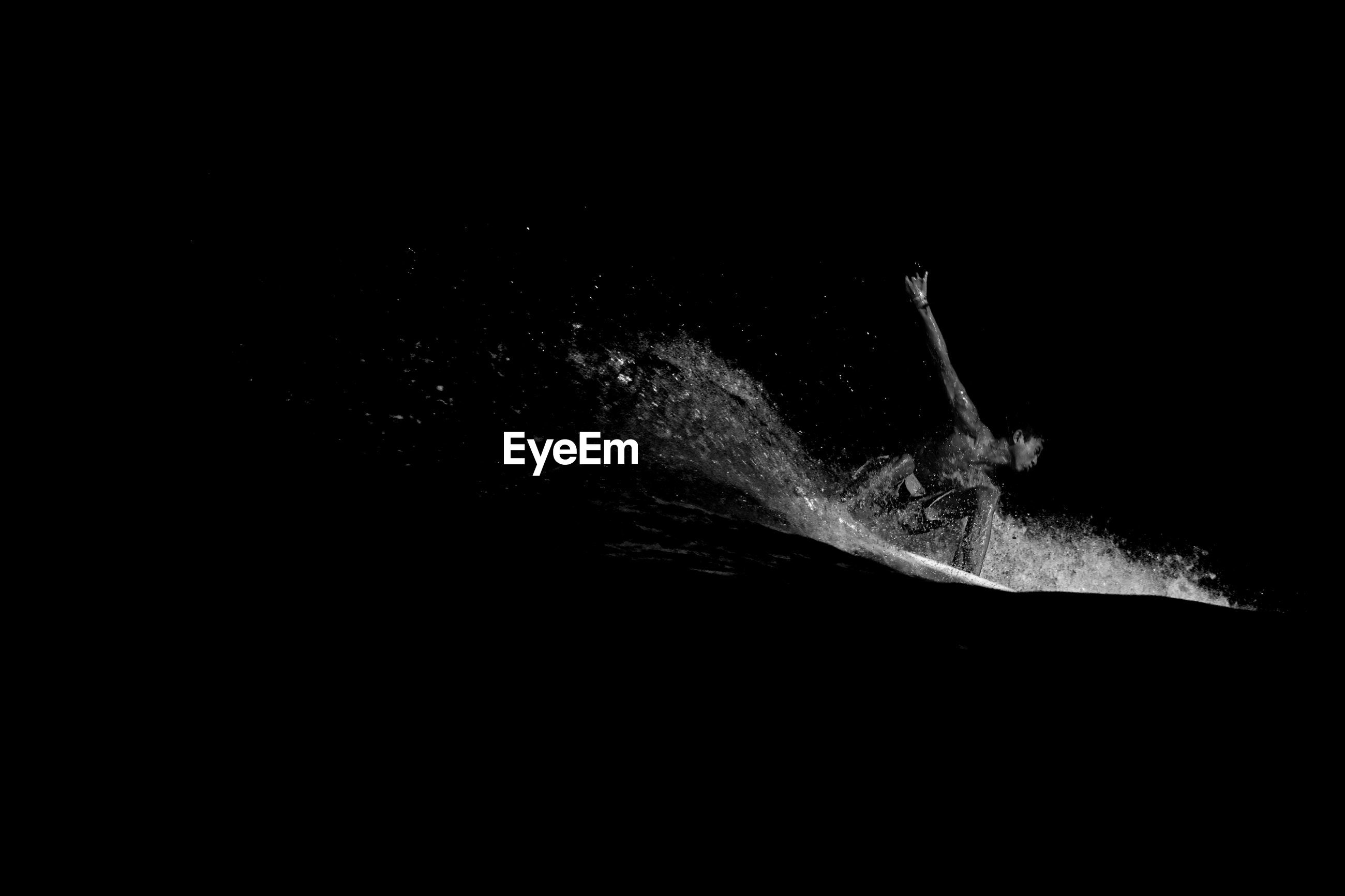 Man surfing in sea at night