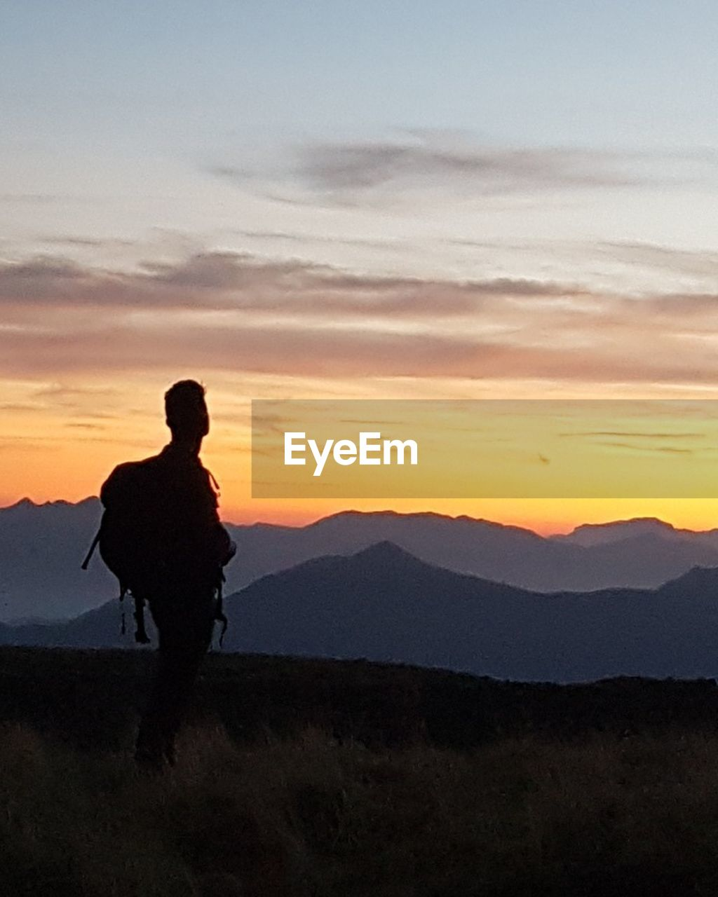 sunset, silhouette, nature, mountain, beauty in nature, sky, real people, one person, scenics, landscape, leisure activity, tranquil scene, tranquility, outdoors, standing, men, full length, cloud - sky, mountain range, lifestyles, hiking, adventure, one man only, day, people