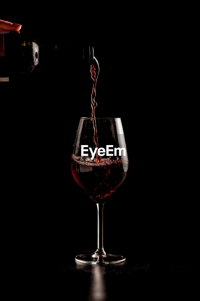 GLASS OF WINE ON TABLE AGAINST BLACK BACKGROUND