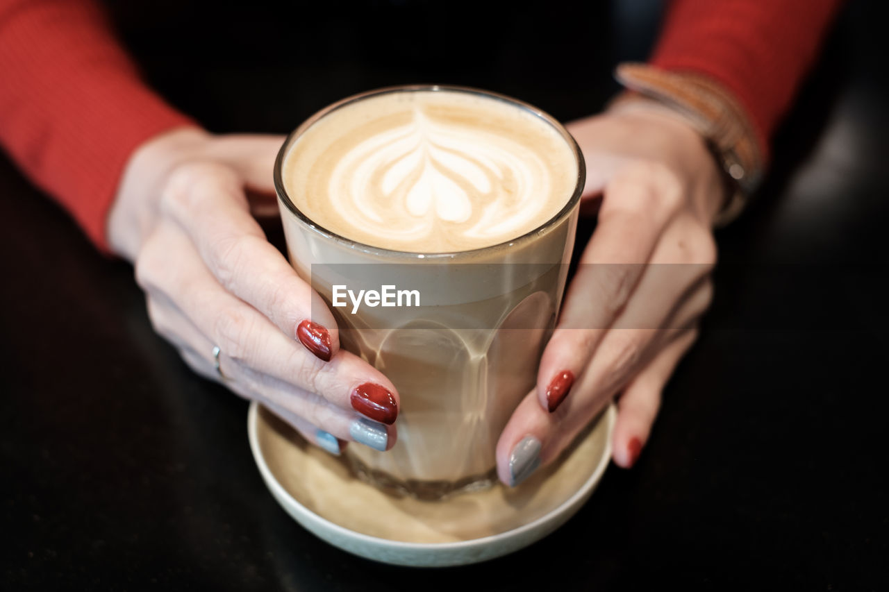 Cropped hands of woman holding coffee cup on table