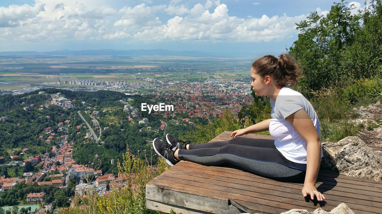 Side view of young woman sitting on pier overlooking cityscape