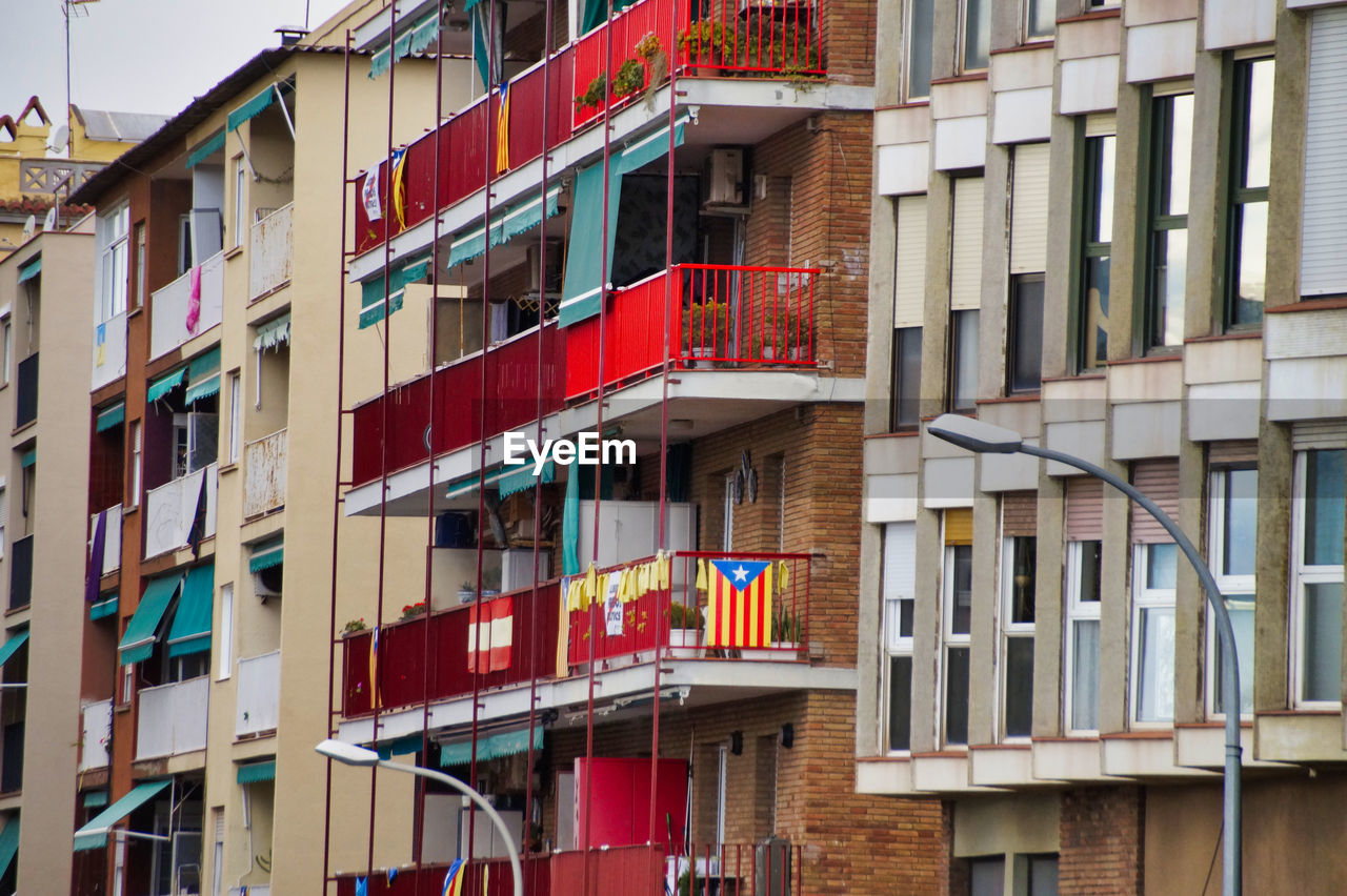 building exterior, built structure, architecture, building, window, multi colored, no people, day, city, flag, patriotism, low angle view, outdoors, balcony, striped, residential district, red, full frame, hanging, apartment