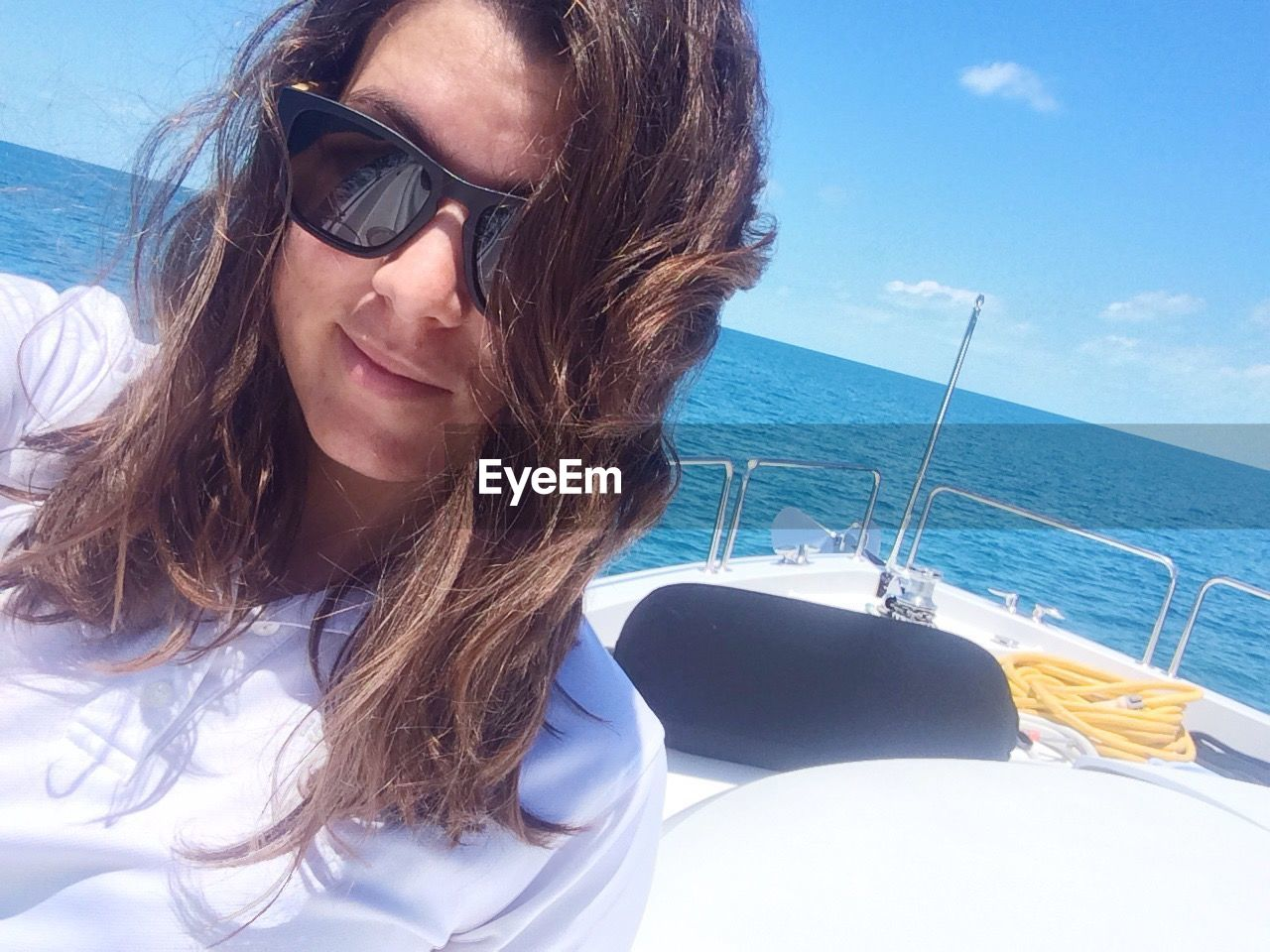 Portrait Of Young Woman On Boat At Sea Against Blue Sky