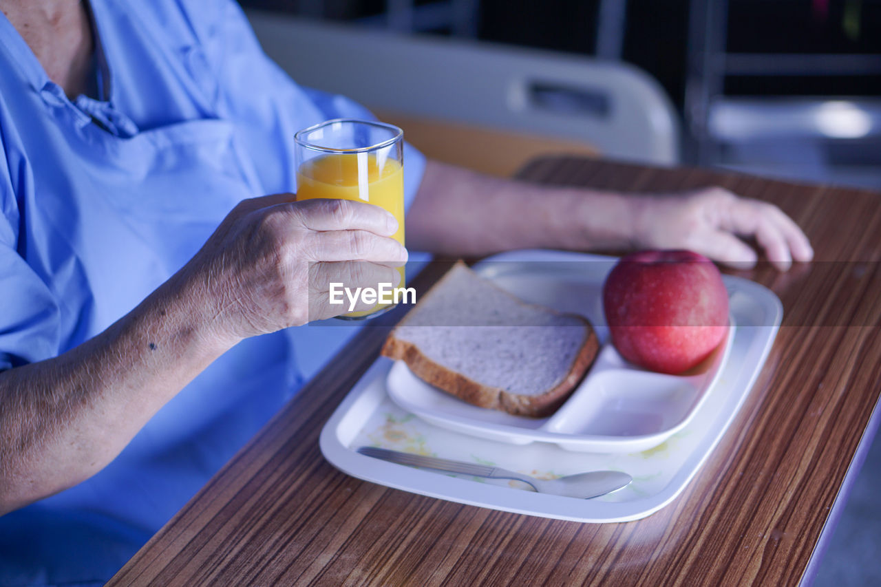 food and drink, table, food, real people, drink, human hand, drinking glass, freshness, two people, bread, indoors, plate, breakfast, healthy eating, men, close-up, orange juice, day, ready-to-eat, people