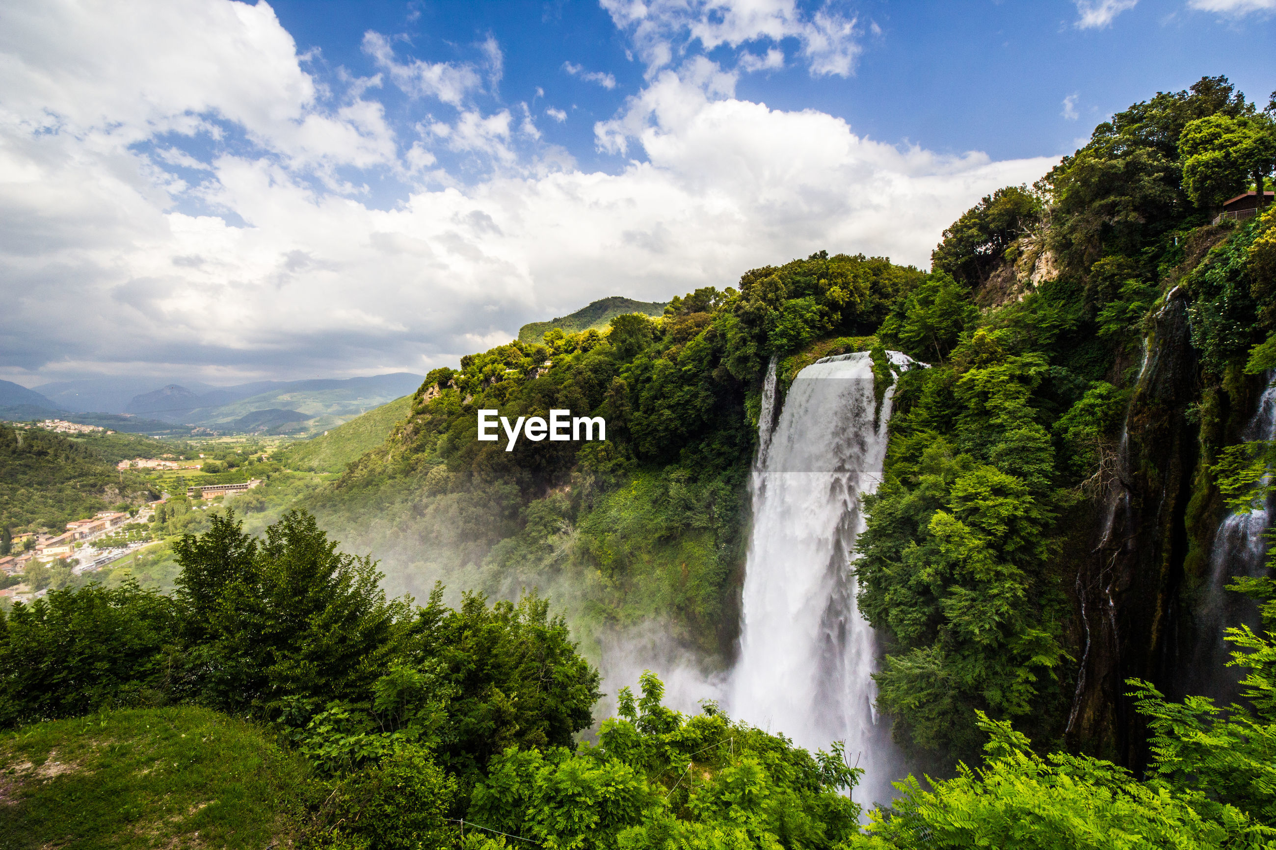 SCENIC VIEW OF WATERFALL IN FOREST AGAINST CLOUDY SKY