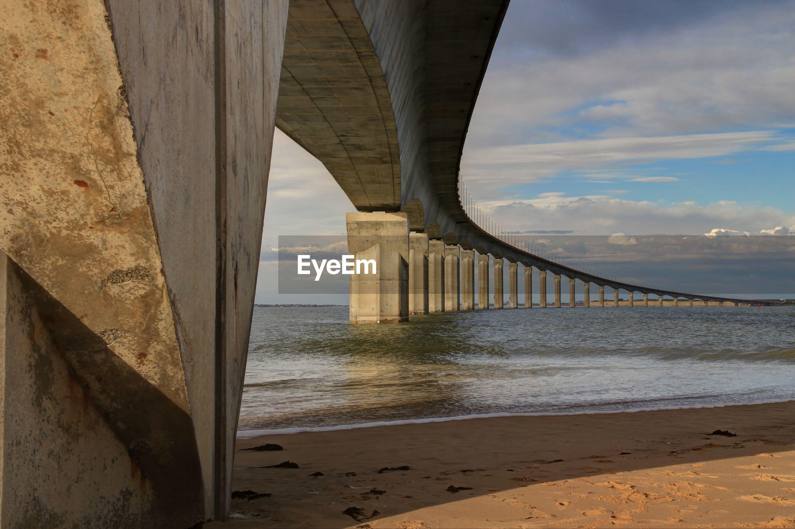 Bridge at beach against sky
