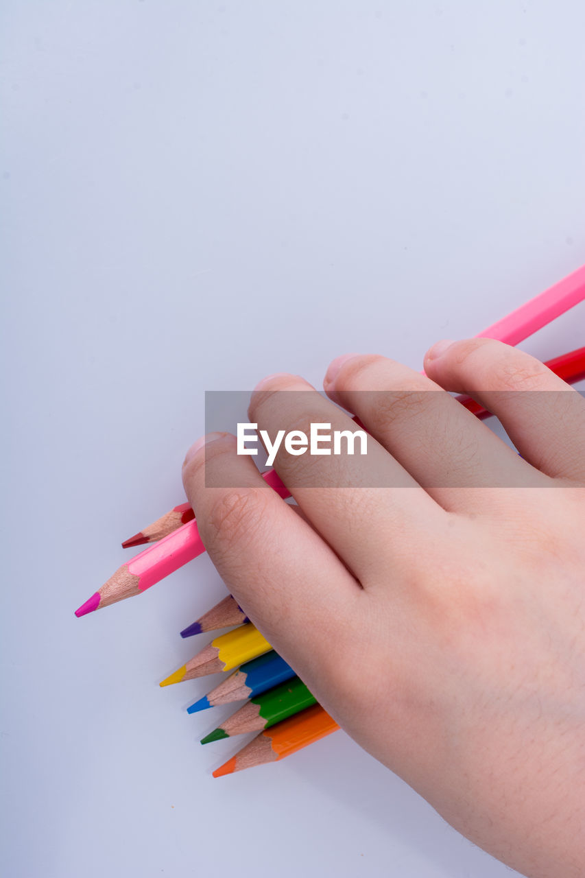 human hand, multi colored, human body part, art and craft, hand, pencil, creativity, indoors, body part, one person, finger, human finger, close-up, writing instrument, colored pencil, studio shot, craft, choice, unrecognizable person, art and craft equipment