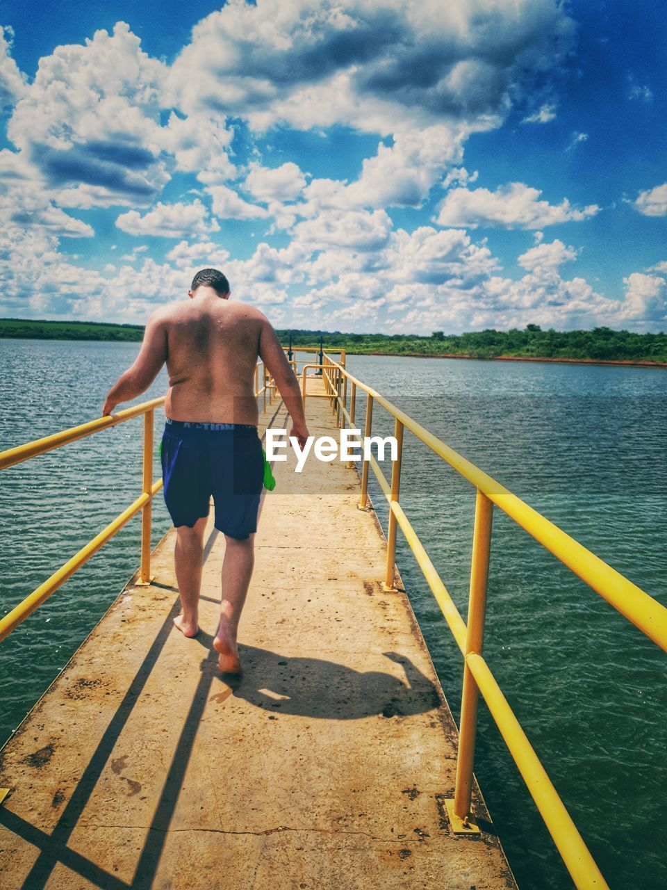water, cloud - sky, railing, sky, one person, rear view, full length, real people, nature, lifestyles, sea, leisure activity, standing, day, beauty in nature, staircase, shirtless, walking, outdoors, shorts